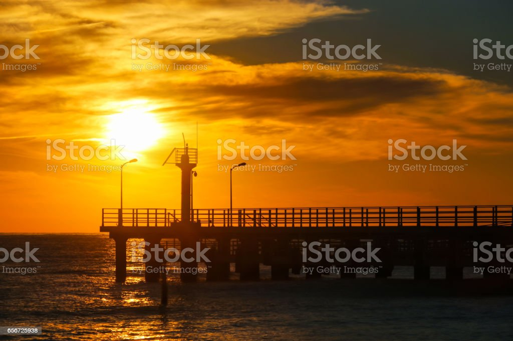 Sunny sunset through the pier stock photo