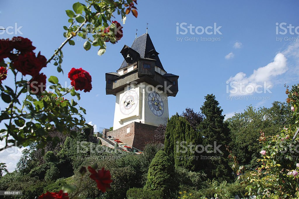 Sunny view of a clock tower and flowers in Graz Uhrturm stock photo