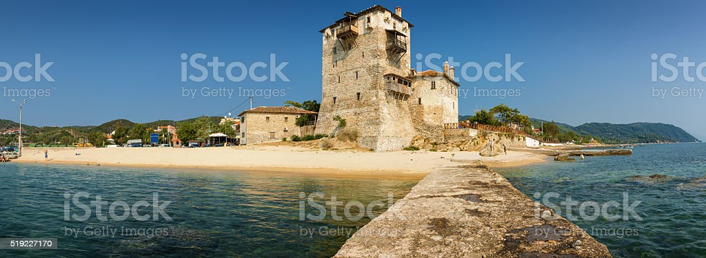 Sunny view of tower in Uranopolis bay from pier, Greece. stock photo