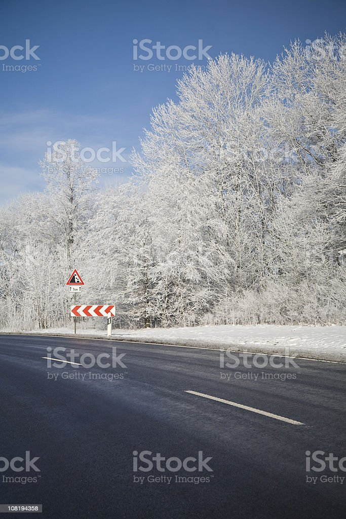 Sunny Winter Day with Ice Covered Road and Danger Sign royalty-free stock photo