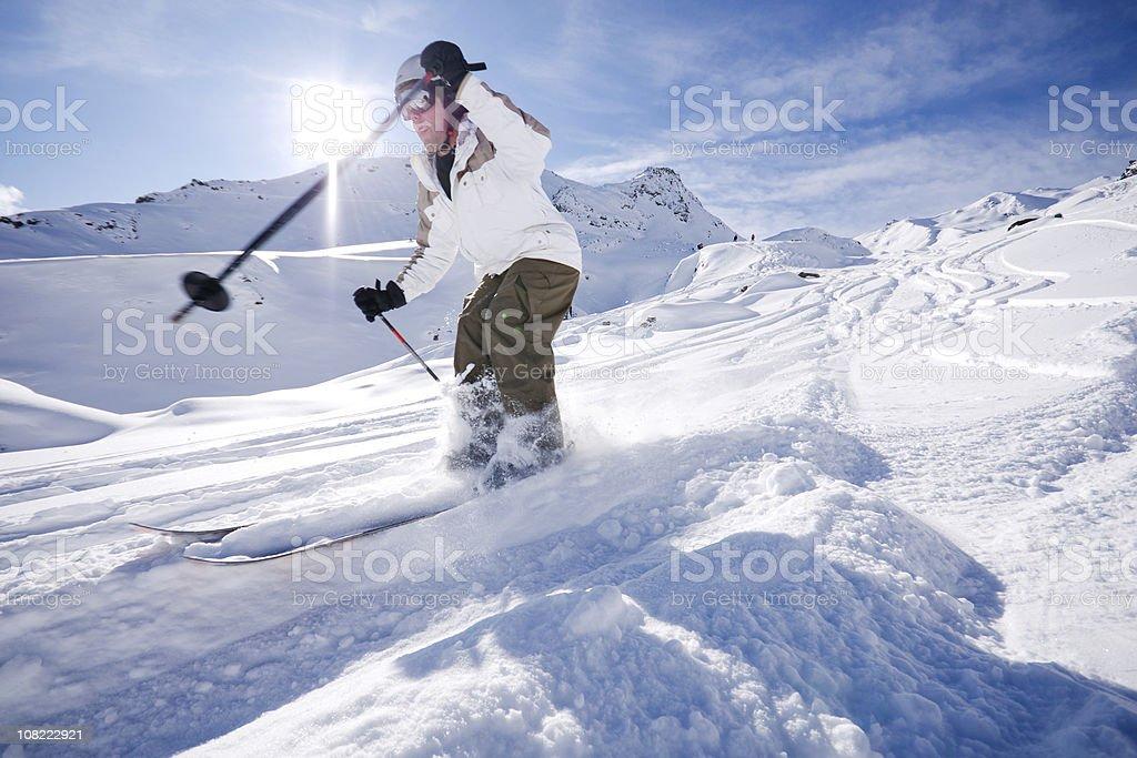 Skier cutting deep trails in powder snow high in the Alpine back...