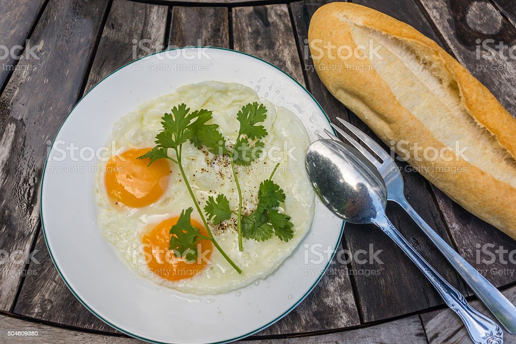 Sunny-side up eggs and loaf of bread on wooden table stock photo