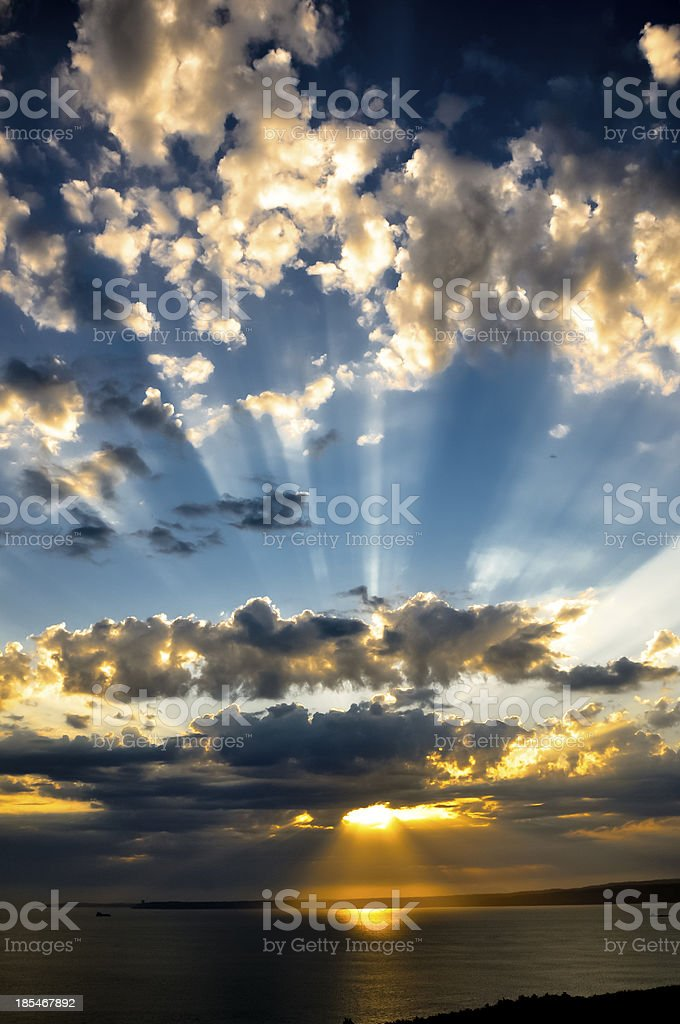 sunrays at sunset with clouds lights trace sunbeams. royalty-free stock photo