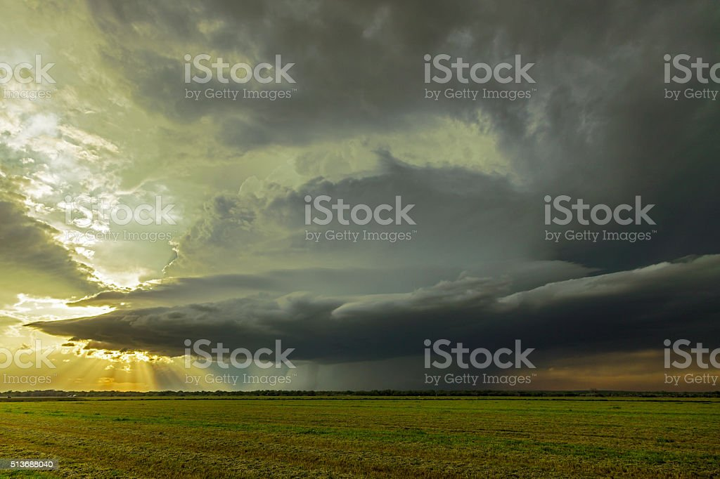 Sunrays emerge from dark, threatening thunderstorm with tornado stock photo