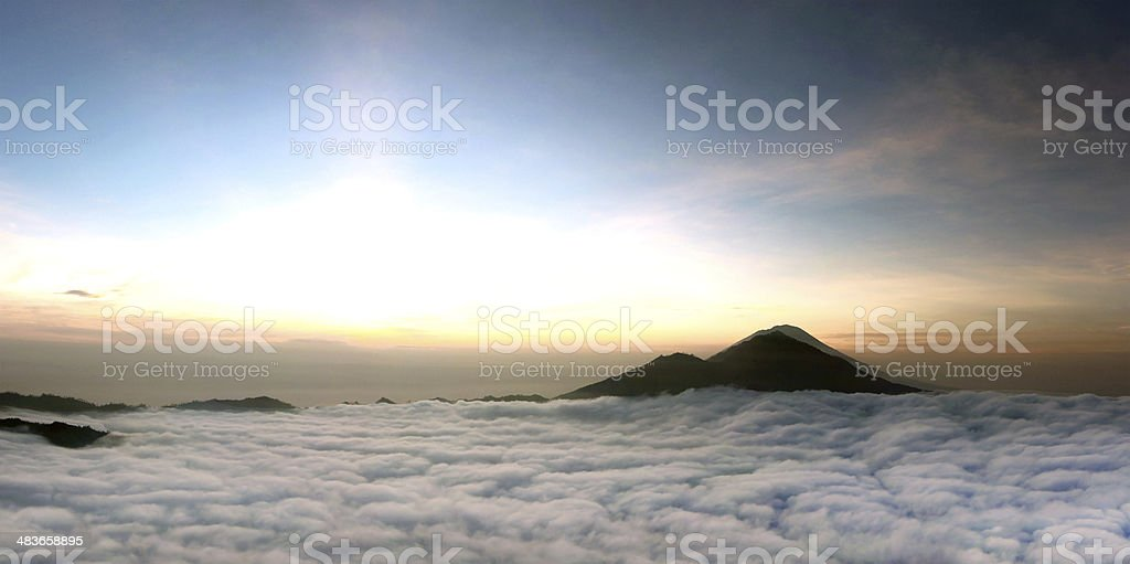 Sunrise above clouds with a mountain volcano view stock photo