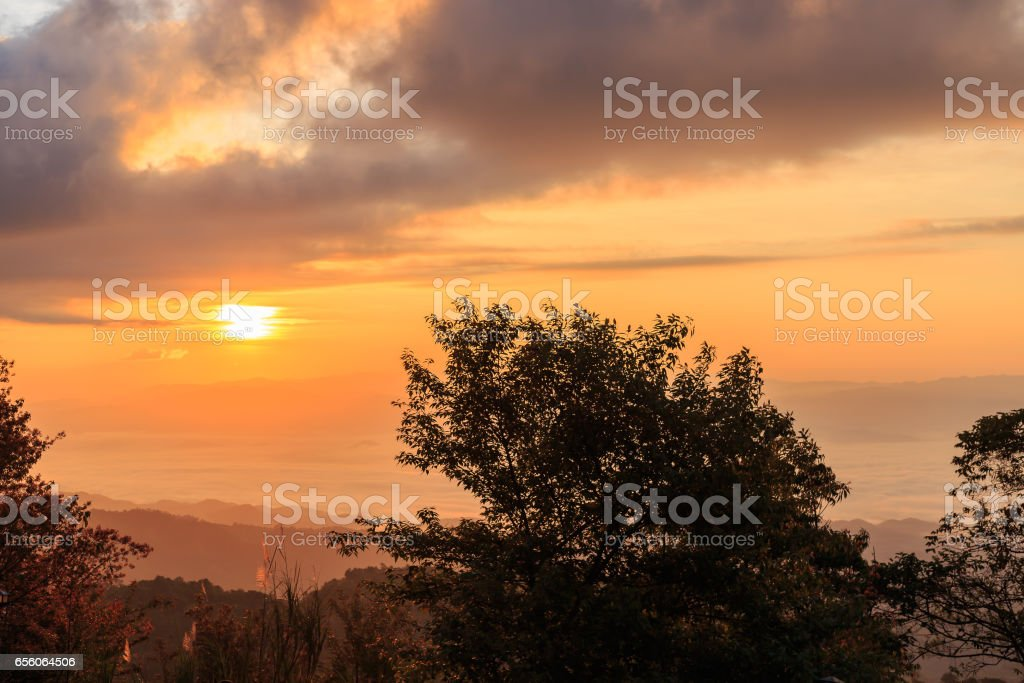 Sunrise at mountain terrain in a sea of mist, on cloudy sky. Beautiful panoramic view of highland. stock photo