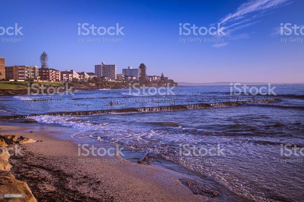 Sunrise at rocky beach in urban Australia stock photo