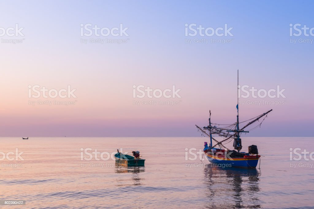 Sunrise at the Sea with fisher boats and cloudy sky stock photo