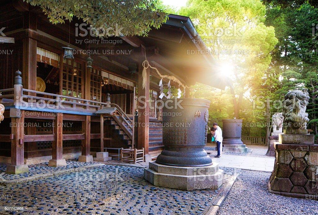Sunrise at Utsunomiya Futarasan Shrine with people praying stock photo