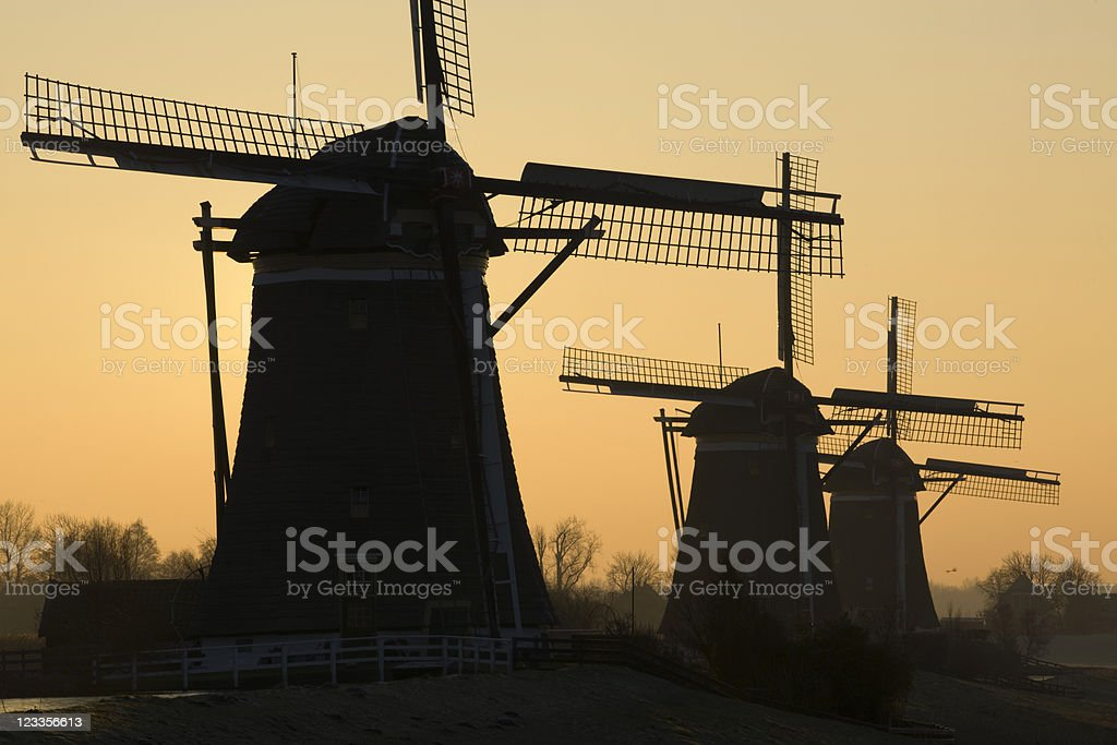sunrise behind a group of traditional Dutch windmills stock photo