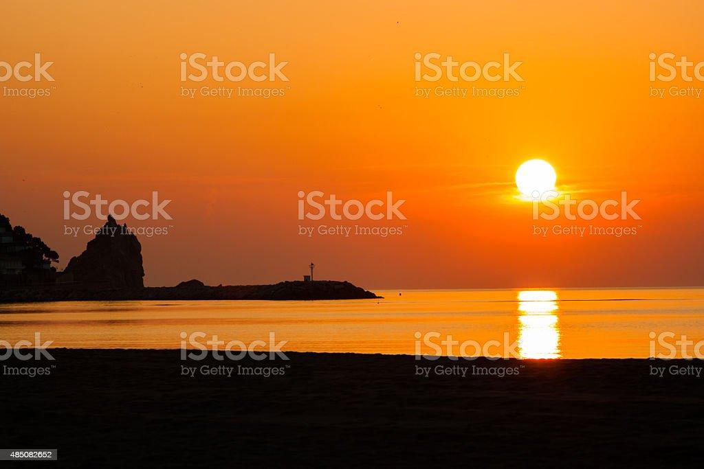 Sunrise by a breakwater. stock photo