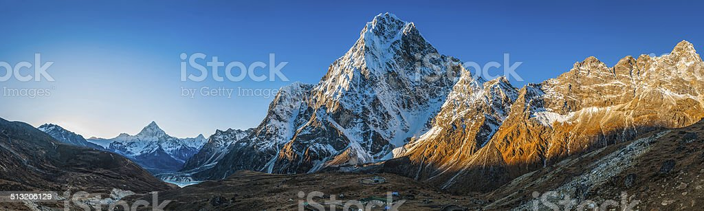 Sunrise in the Himalayas over dramatic mountain peaks glaciers panorama stock photo