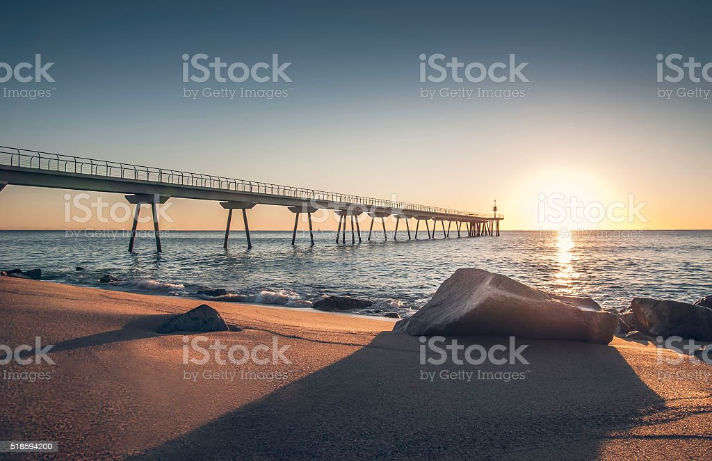 Sunrise on a beach with rocks and bridge stock photo