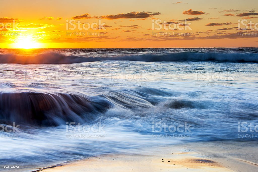 sunrise on Arniston beach with wave motion in south africa stock photo