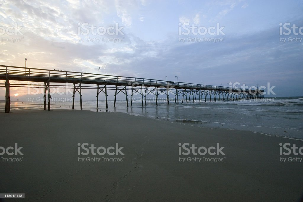 Sunrise on the Beach over a Fishing Pier royalty-free stock photo