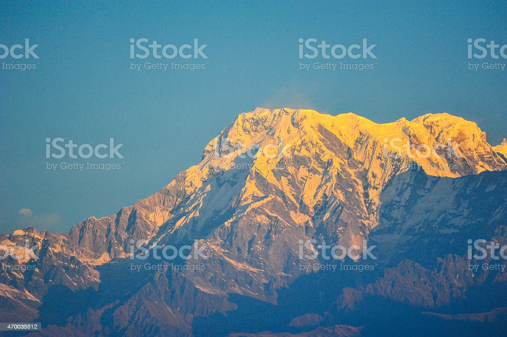 Sunrise on top of the snow mountain against blue sky stock photo
