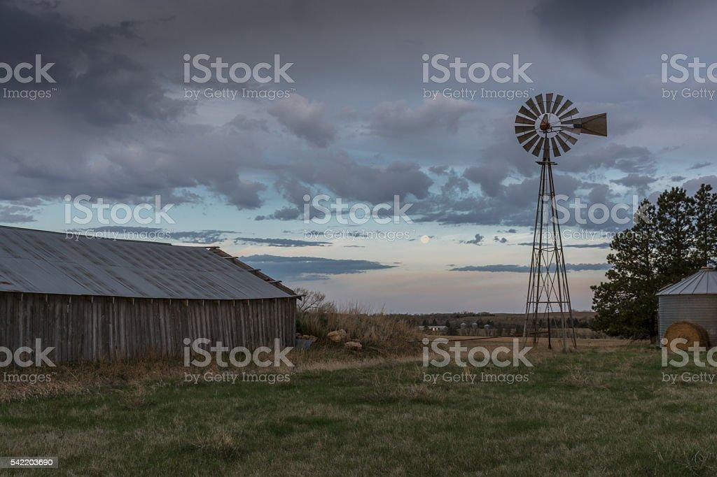 Sunrise on Windmill and Old Barn in South Dakota stock photo