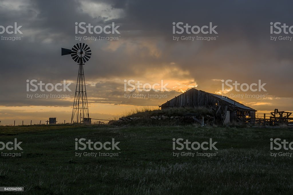 Sunrise on Windmill and Old Barn in South Dakota stock photo