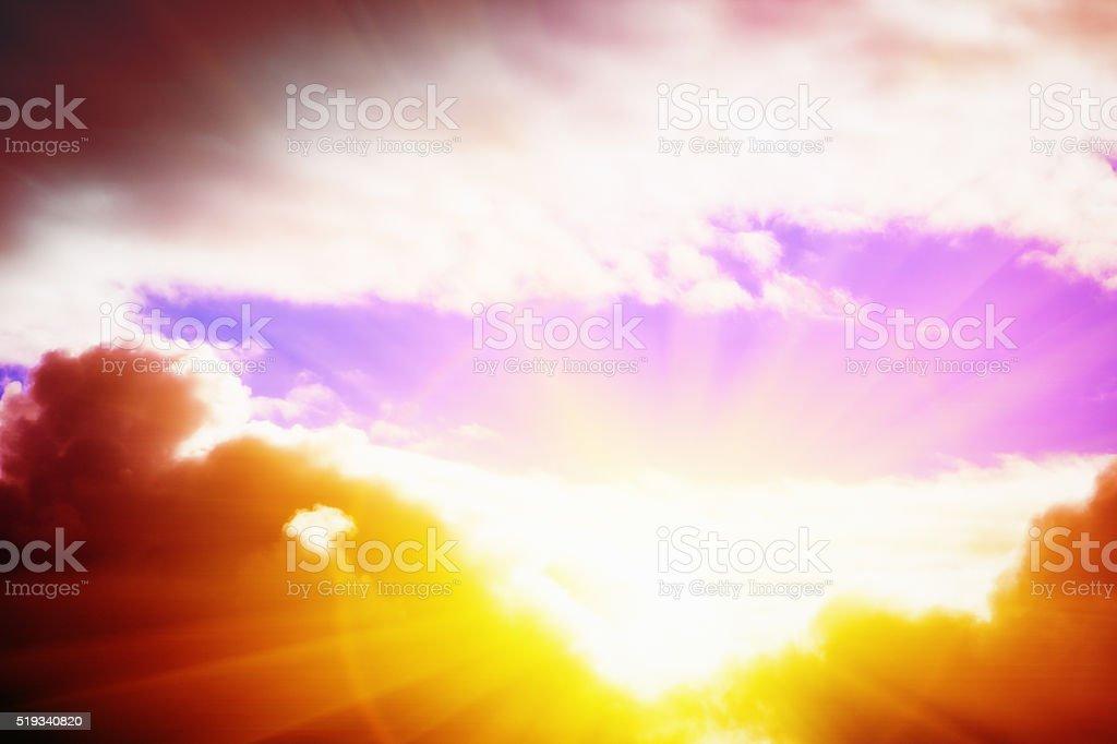 Sunrise or sunset creating dazzling rays peeping through vivid clouds stock photo