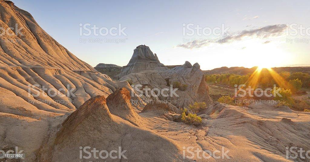 sunrise over barren badlands landscape stock photo