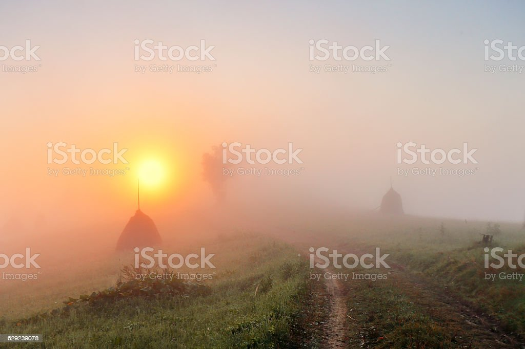 Sunrise over mountain field. Haystacks and road  in misty autumn stock photo