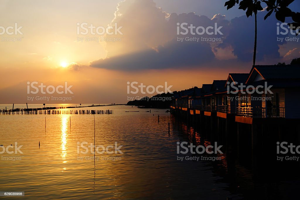 Sunrise over ocean bungalows on a cloudy day stock photo