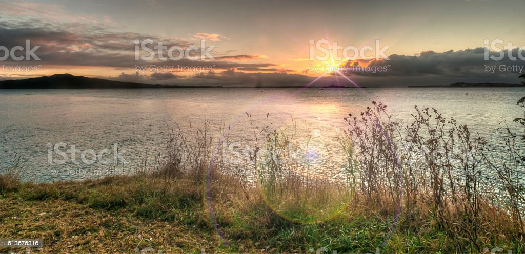 Sunrise over Rangitoto with flare stock photo