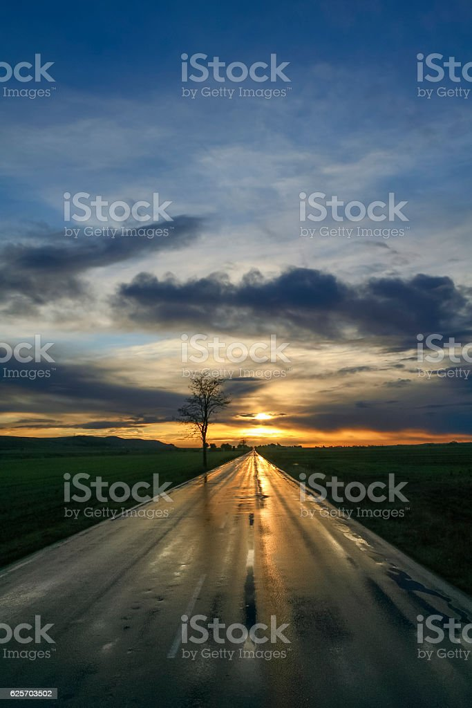 Sunrise reflected on the countryside wet road after the rain.Italy stock photo