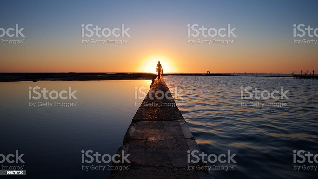 Sunrise Silhouette of a Person at a Tidal Pool stock photo