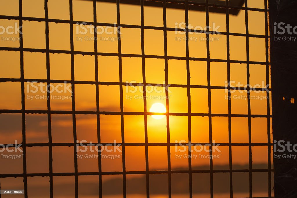 Sunrise sun behind a metal grid stock photo