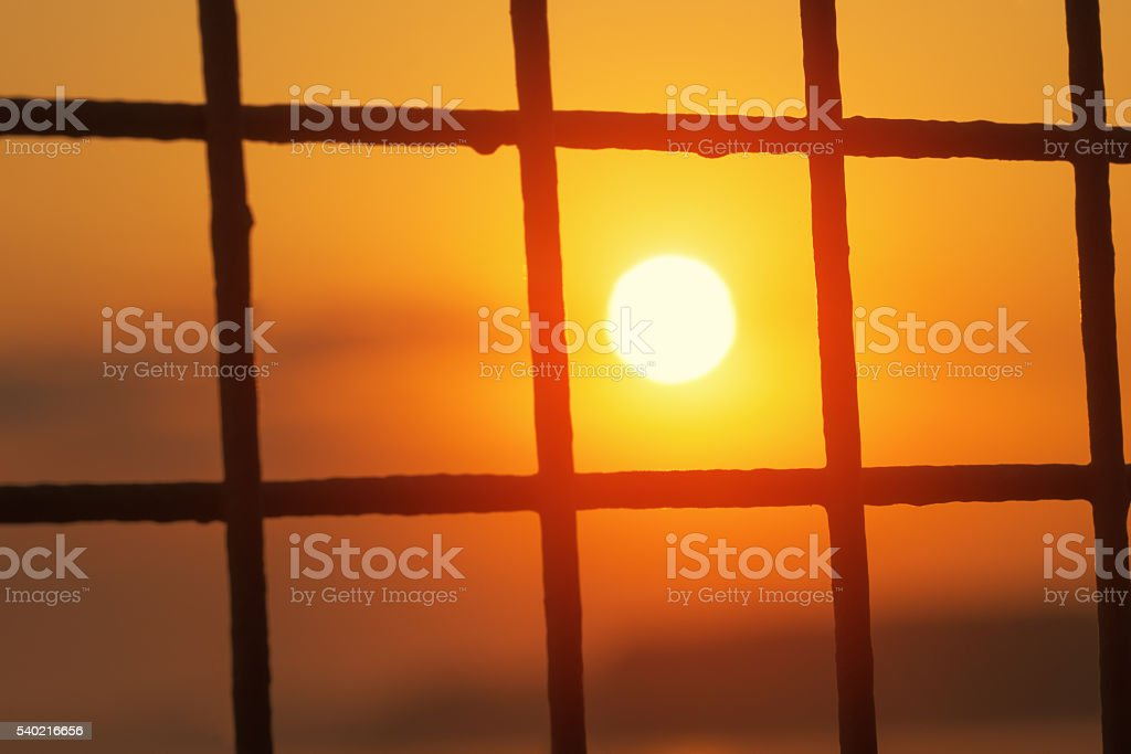Sunrise sun inside of metal grid cell stock photo