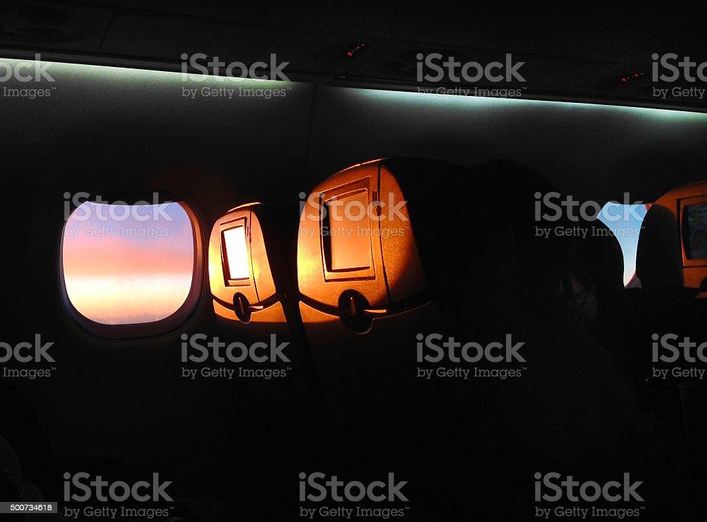 sunrise through airplane window stock photo