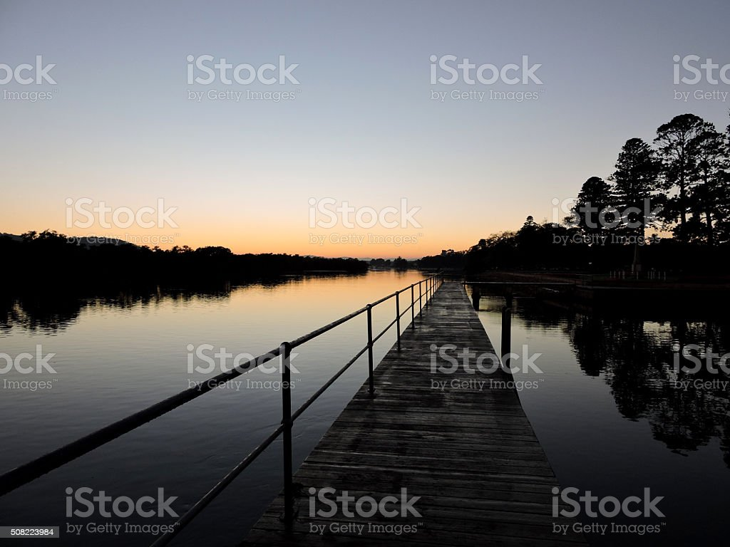 Sunrise waterscape with wharf and tree reflections stock photo