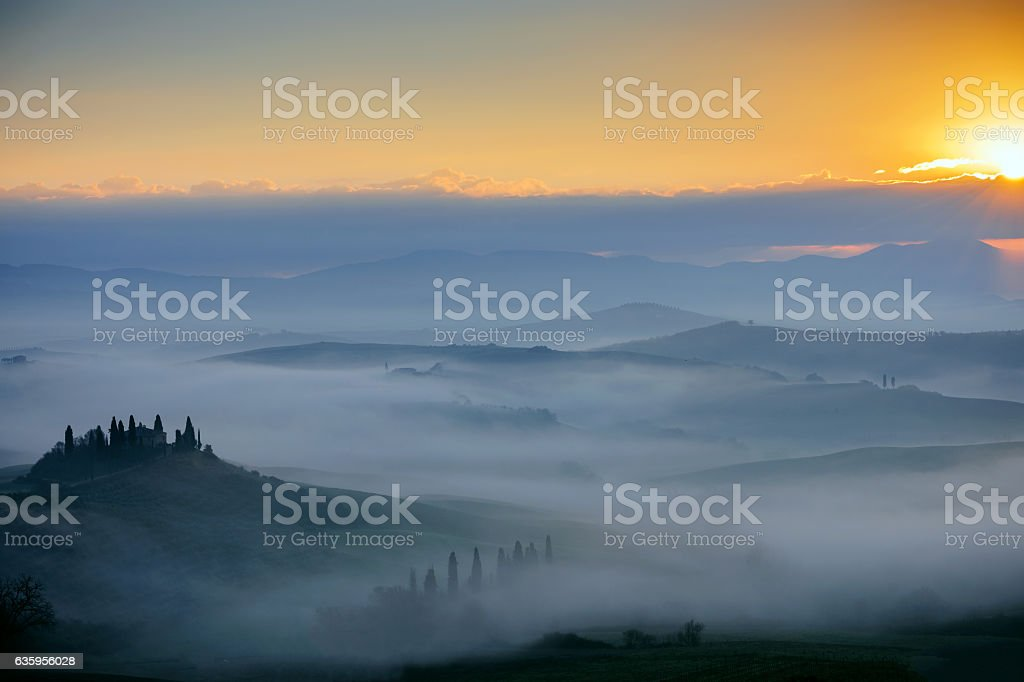 Sunrise with rays over the misty valleys in Tuscany,Italy. stock photo