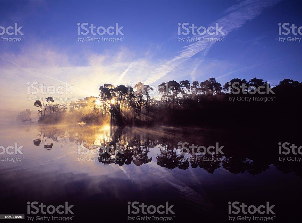 Sunrise with sun breaking through fog at Lake Esch. stock photo
