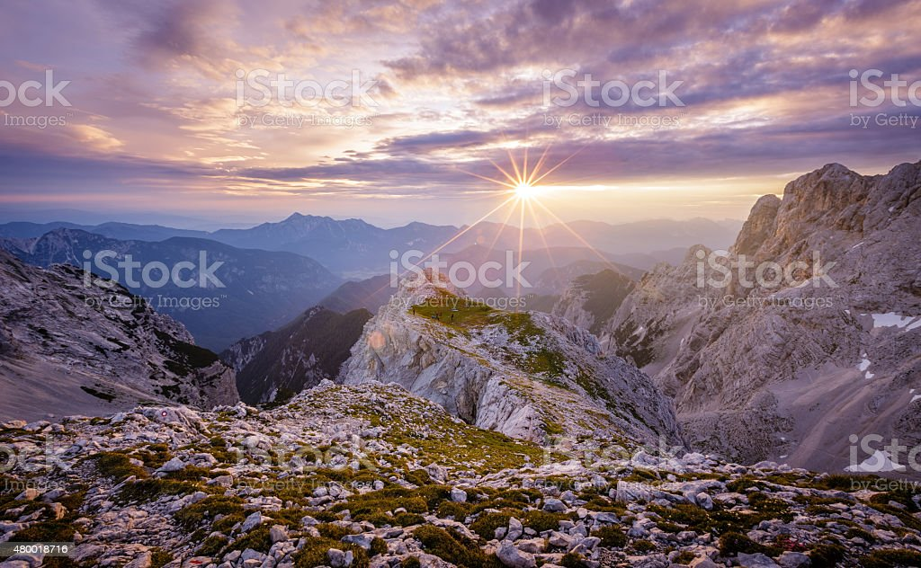 Sunrise with sun star between clouds in the Julian Alps stock photo