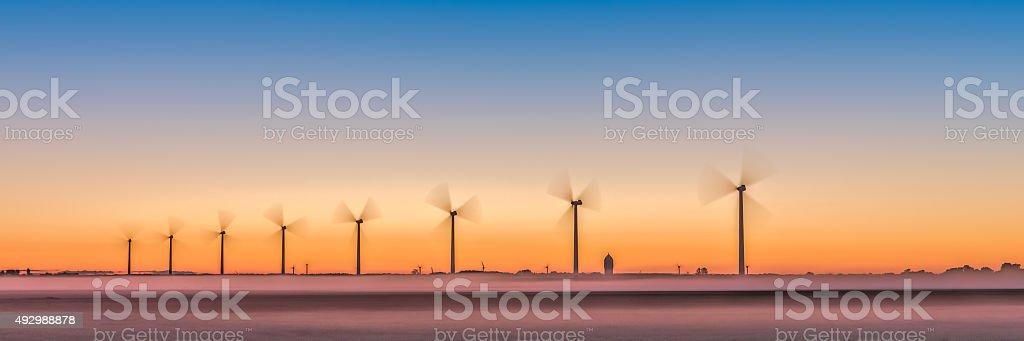 sunrise with wind turbine stock photo