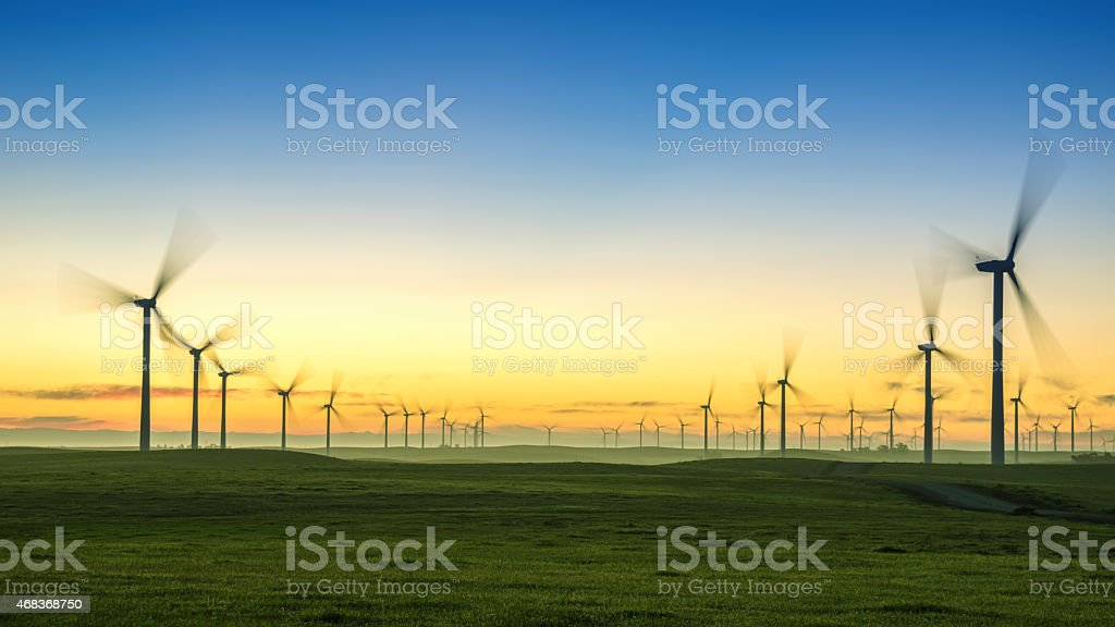 Sunrise With Wind Turbines and Green Grass stock photo