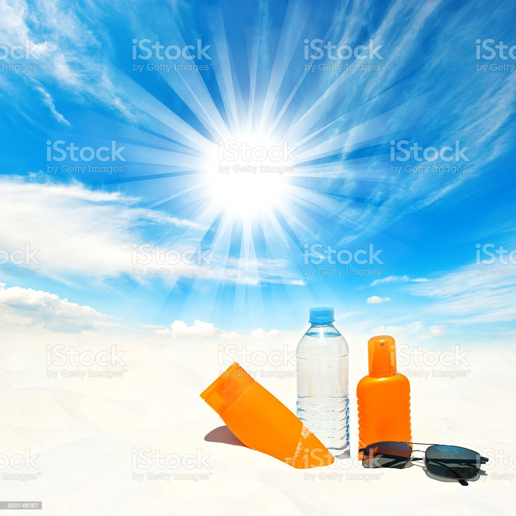 Sunscreen cream and bottle of water over sunny blue sky stock photo