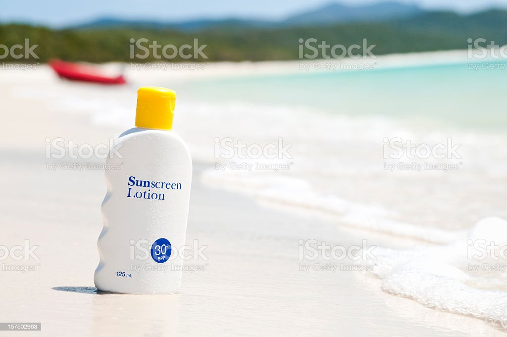 Sunscreen lotion on the beach stock photo
