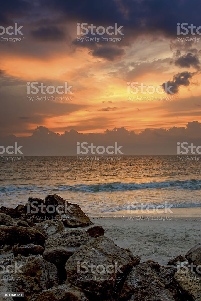 sunset above a rocky beach stock photo