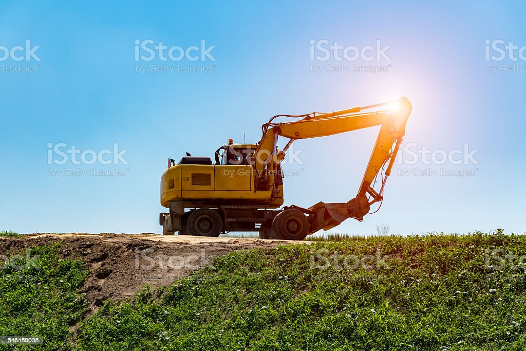 Sunset above excavator working on the construction site stock photo