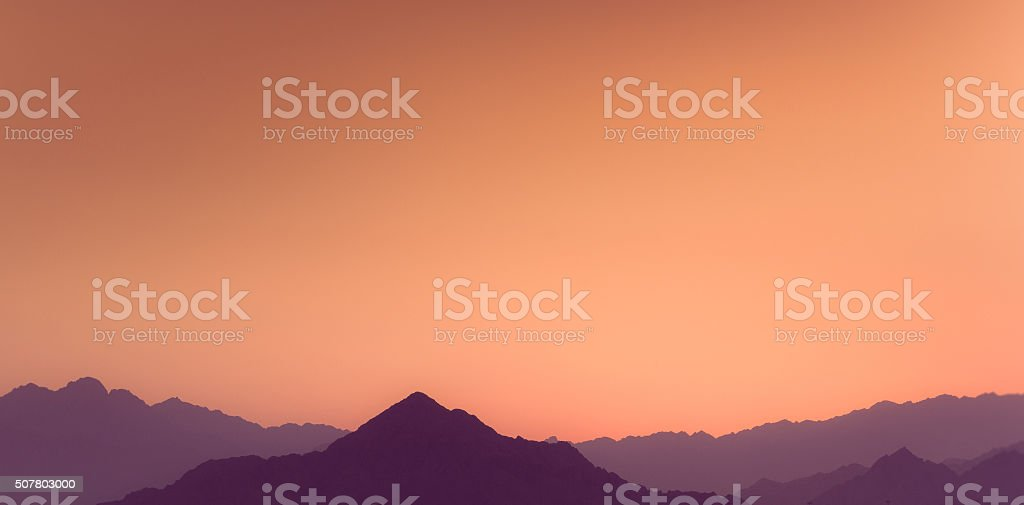 Sunset above layers of mountains. stock photo