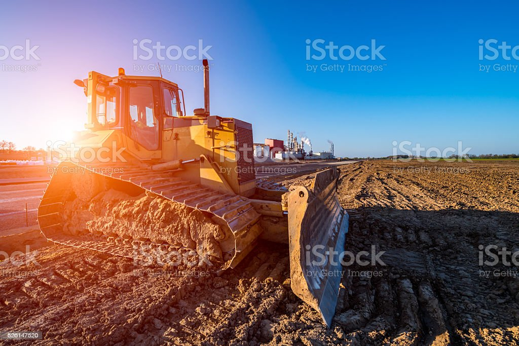 Sunset above the bulldozer working on the construction site stock photo