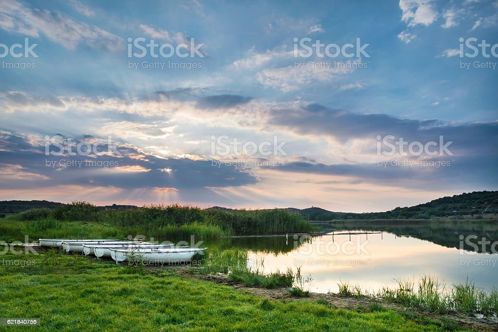 Sunset above the lake with boats stock photo