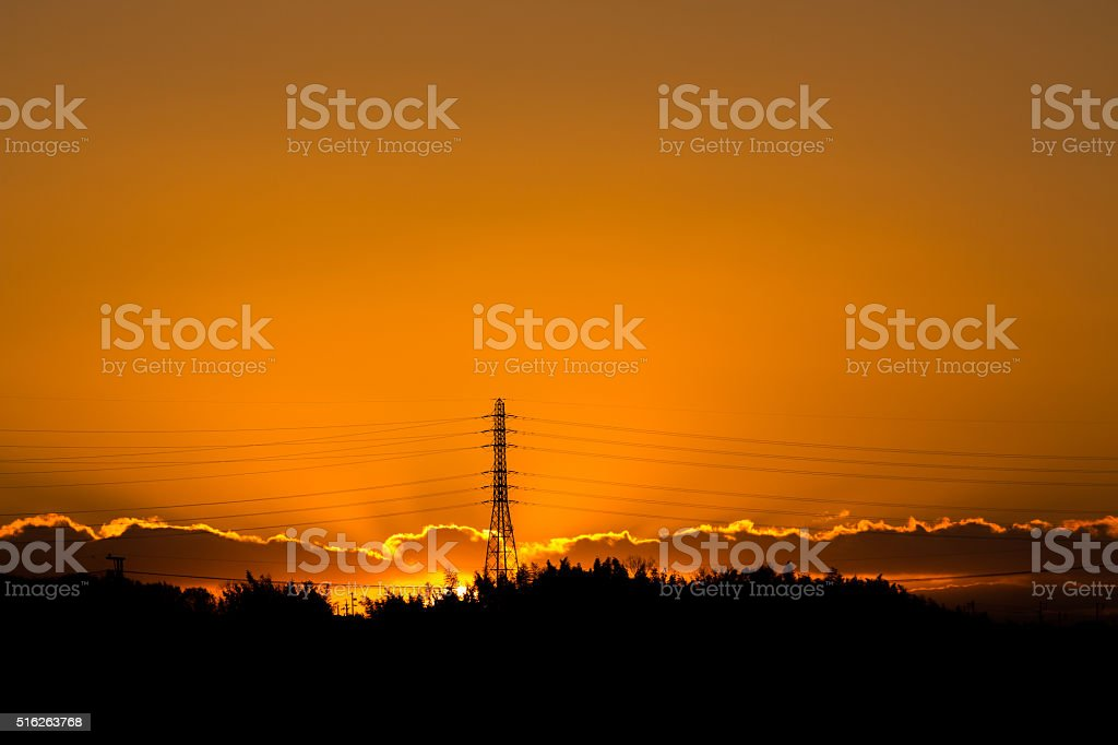 Sunset against electric post. stock photo
