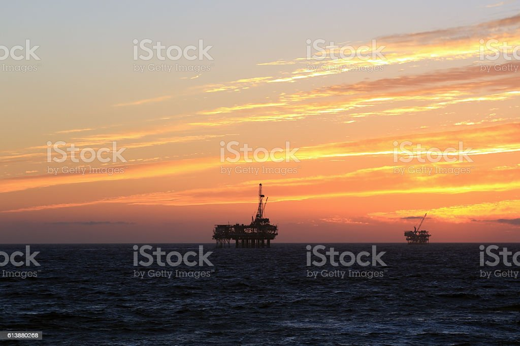 Sunset along California coast with oil rigs stock photo