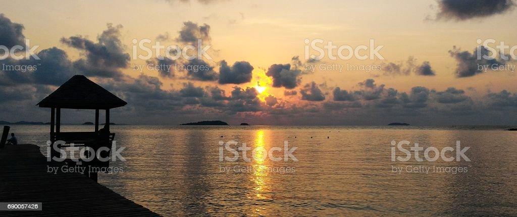 sunset and bridge into sea stock photo