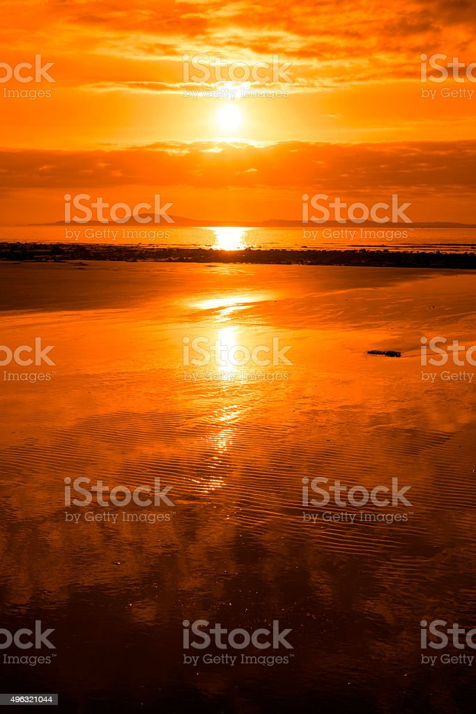 sunset and calm reflections at beal beach stock photo