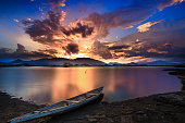 sunset and dramatic sky with old wooden boat